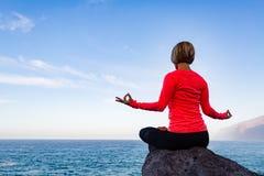 Donna che medita nella posa di yoga, vista di oceano Fotografie Stock