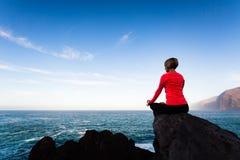 Donna che medita nella posa di yoga, vista di oceano Immagine Stock