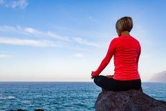 Donna che medita nella posa di yoga, vista di oceano Fotografia Stock Libera da Diritti