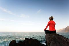 Donna che medita nella posa di yoga, vista di oceano Immagini Stock Libere da Diritti