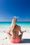 Donna che medita su spiaggia nella posizione di loto Immagini Stock