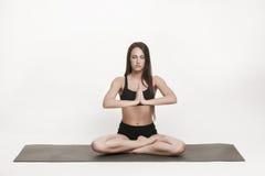 Donna che medita su stuoia di yoga Immagine Stock Libera da Diritti