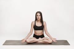 Donna che medita su stuoia di yoga Immagini Stock Libere da Diritti