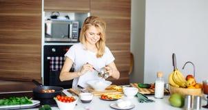 Donna che mescola gli ingredienti deliziosi dell'insalata del superfood con i cucchiai di legno in cucina Fotografia Stock Libera da Diritti