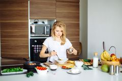 Donna che mescola gli ingredienti deliziosi dell'insalata del superfood con i cucchiai di legno in cucina Immagini Stock Libere da Diritti