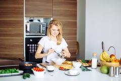 Donna che mescola gli ingredienti deliziosi dell'insalata del superfood con i cucchiai di legno in cucina Fotografia Stock