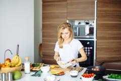 Donna che mescola gli ingredienti deliziosi dell'insalata del superfood con i cucchiai di legno in cucina Immagini Stock