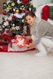 Donna che mette casella attuale sotto l'albero di Natale Fotografia Stock