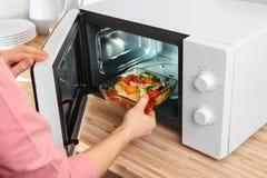 Donna che mette ciotola con le verdure in forno a microonde Immagine Stock Libera da Diritti
