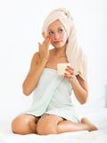 Donna che mette crema sul fronte Immagine Stock Libera da Diritti