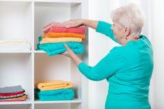 Donna che mette gli asciugamani allo scaffale Fotografia Stock