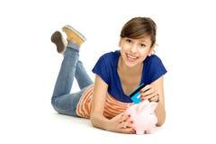 Donna che mette la carta di credito nella banca piggy Immagini Stock Libere da Diritti