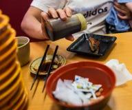 Donna che mette la salsa di soia sui sushi fotografia stock