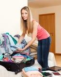 Donna che mette le cose in una valigia Fotografie Stock