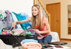 Donna che mette le cose in una valigia aperta Immagini Stock Libere da Diritti