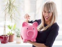 Donna che mette moneta nel porcellino salvadanaio immagine stock