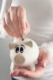 Donna che mette moneta nella banca di moneta di porcellino Immagine Stock