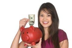 Donna che mette soldi nella banca piggy Immagine Stock Libera da Diritti