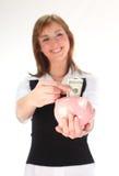 Donna che mette soldi nella Banca Piggy fotografia stock libera da diritti