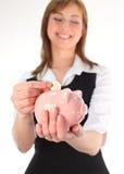 Donna che mette soldi nella Banca Piggy fotografie stock libere da diritti