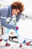 Donna che mette sui pattini di rullo all'aperto Fotografia Stock Libera da Diritti