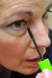 Donna che mette sul eyeliner immagini stock