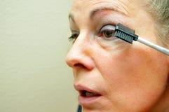 Donna che mette sul eyeliner fotografia stock libera da diritti