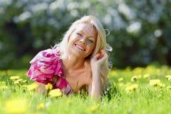 Donna che mette sul prato del fiore Fotografia Stock