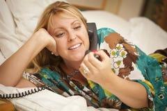 Donna che mette sul suo letto facendo uso del telefono Fotografia Stock