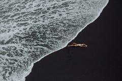Donna che mette sulla sabbia tropicale del nero della spiaggia in bikini bianco immagine stock libera da diritti