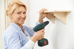 Donna che mette sullo scaffale di legno a casa facendo uso del trapano senza cordone Immagini Stock Libere da Diritti