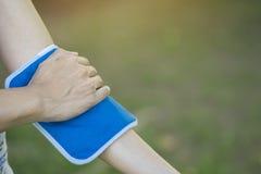 Donna che mette un pack sul suo dolore del braccio Immagini Stock