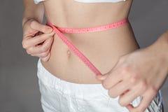 Donna che misura il suo corpo sottile fotografia stock