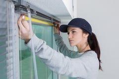 Donna che misura per i ciechi di finestra fotografie stock libere da diritti