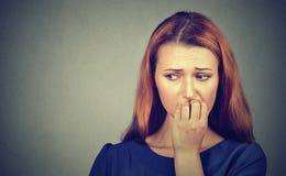 Donna che morde le sue unghie che hanno bisogno qualcosa o ansioso nervosa Immagine Stock