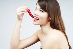 Donna che morde un pepe di peperoncino rosso Immagini Stock