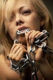 Donna che morde una catena del bicromato di potassio sopra Fotografie Stock Libere da Diritti