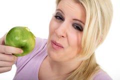 Donna che morde in una mela acida fotografia stock libera da diritti