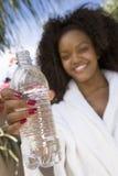 Donna che mostra bottiglia di acqua fotografie stock libere da diritti
