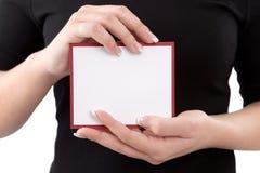 Donna che mostra carta in bianco o cartello in sue mani Fotografie Stock Libere da Diritti
