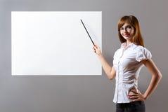 Donna che mostra con l'indicatore al cartello in bianco Immagini Stock Libere da Diritti