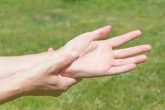 Donna che mostra dolore delle mani Fotografia Stock