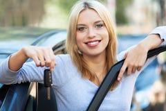 Donna che mostra fuori i nuovi tasti dell'automobile Immagini Stock