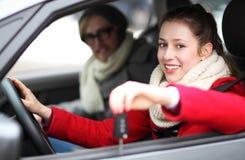 Donna che mostra fuori i nuovi tasti dell'automobile Fotografia Stock Libera da Diritti