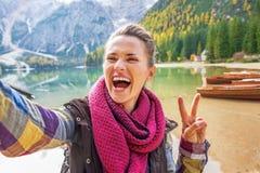 Donna che mostra gesto di vittoria mentre facendo selfie Immagini Stock Libere da Diritti