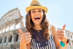 Donna che mostra i pollici su davanti al colosseum Fotografie Stock