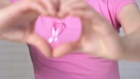 Donna che mostra il nastro di consapevolezza del cancro al seno dell'inquadratura del segno del cuore - concetto di consapevolezz archivi video
