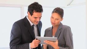 Donna che mostra la sua compressa ad un uomo d'affari video d archivio