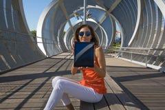 Donna che mostra lo schermo della compressa che si siede al posto moderno nella città Fotografie Stock