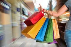 Donna che mostra pollice su e che tiene i sacchetti della spesa Fotografia Stock